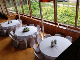 three dining tables next to the huge glass windows